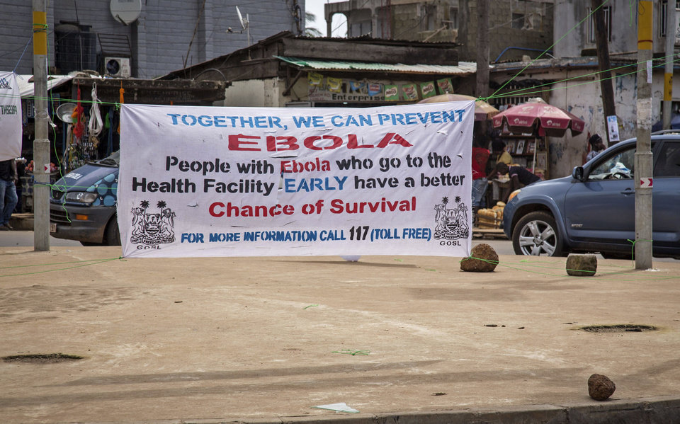 Photo - A banner encouraging people suffering from Ebola to go immediately to a health center for treatment is seen on a sidewalk in the city of  Freetown, Sierra Leone, Thursday, Aug. 7, 2014. While the Ebola virus outbreak has now reached four countries, Liberia and Sierra Leone account for more than 60 percent of the deaths, according to the World Health Organization. The outbreak that emerged in March has claimed at least 932 lives. (AP Photo/Michael Duff)