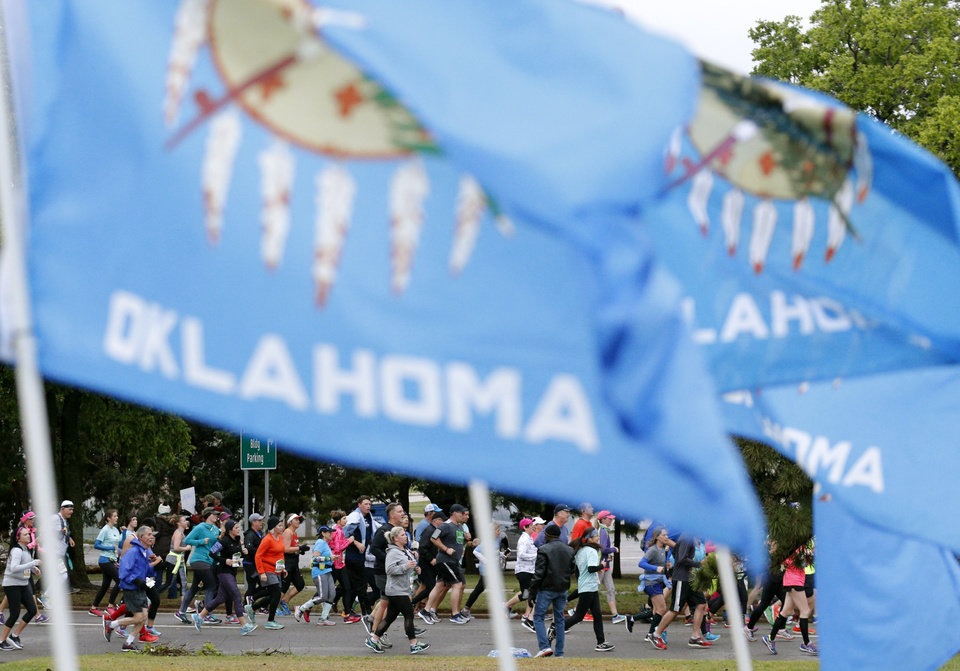 Photo -  Runners stream past Oklahoma flags near the state Capitol during the 2017 Oklahoma City Memorial Marathon on April 30, 2017. [PHOTO BY SARAH PHIPPS, THE OKLAHOMAN]