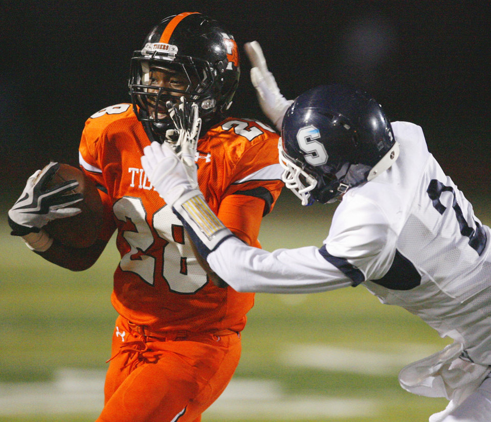 Photo - Tiger Donovan Roberts (28) carries pursued by Shawnee's Brayle Brown (2) in high school football at Harve Collins field on Thursday, Sept. 30, 2010, in Norman, Okla.  Photo by Steve Sisney, The Oklahoman