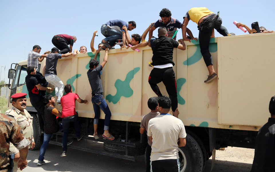 Photo - In this June 14, 2014, photo, Iraqi men board a military truck to join the Iraqi army at the main recruiting center in Baghdad, Iraq, after authorities urged Iraqis to help battle insurgents. U.S. spy agencies are scrambling to close intelligence gaps as they seek to support possible military action against the leaders of the al-Qaida-inspired militant group that has seized parts of Iraq. Intelligence officials are trying to provide options for President Barack Obama as he considers how to counter an insurgency he says poses a threat to Americans.(AP Photo/Karim Kadim, File)