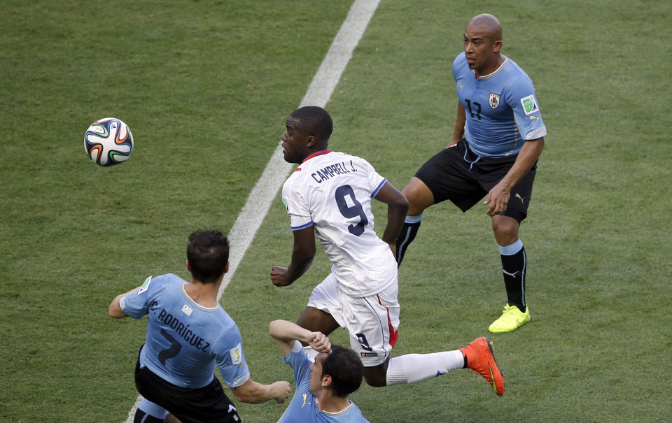 Photo - Costa Rica's Joel Campbell is flanked by Uruguay's Cristian Rodriguez, left, and Uruguay's Egidio Arevalo Rios during the group D World Cup soccer match between Uruguay and Costa Rica at the Arena Castelao in Fortaleza, Brazil, Saturday, June 14, 2014.  (AP Photo/Sergei Grits)