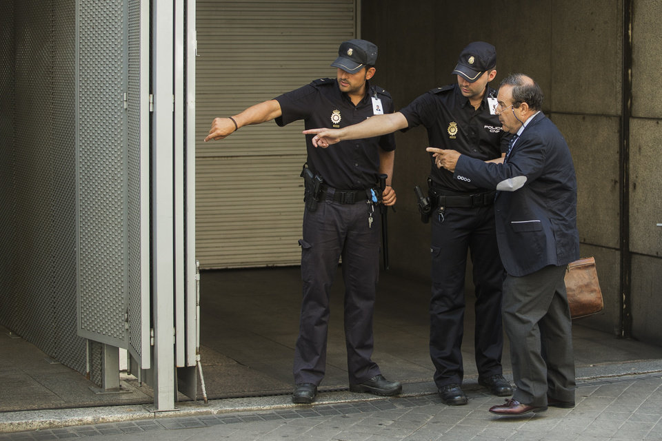 Photo - Ashya King parents's lawyer, Juan Isidro Fernandez Diaz, right, asks police for directions to the entrance as he arrives at the National court in Madrid, Spain, Monday, Sept. 1, 2014. A critically-ill 5-year-old boy driven to Spain by his parents, Brett and Naghemeh, against doctors' advice is receiving medical treatment for a brain tumor in a Spanish hospital as his parents await extradition to Britain, police said Sunday. Officers received a phone call late Saturday from a hotel east of Malaga advising that a vehicle fitting the description circulated by police was on its premises. Both parents were arrested and the boy, Ashya King, was taken to a hospital, a Spanish police spokesman said. (AP Photo/Andres Kudacki)