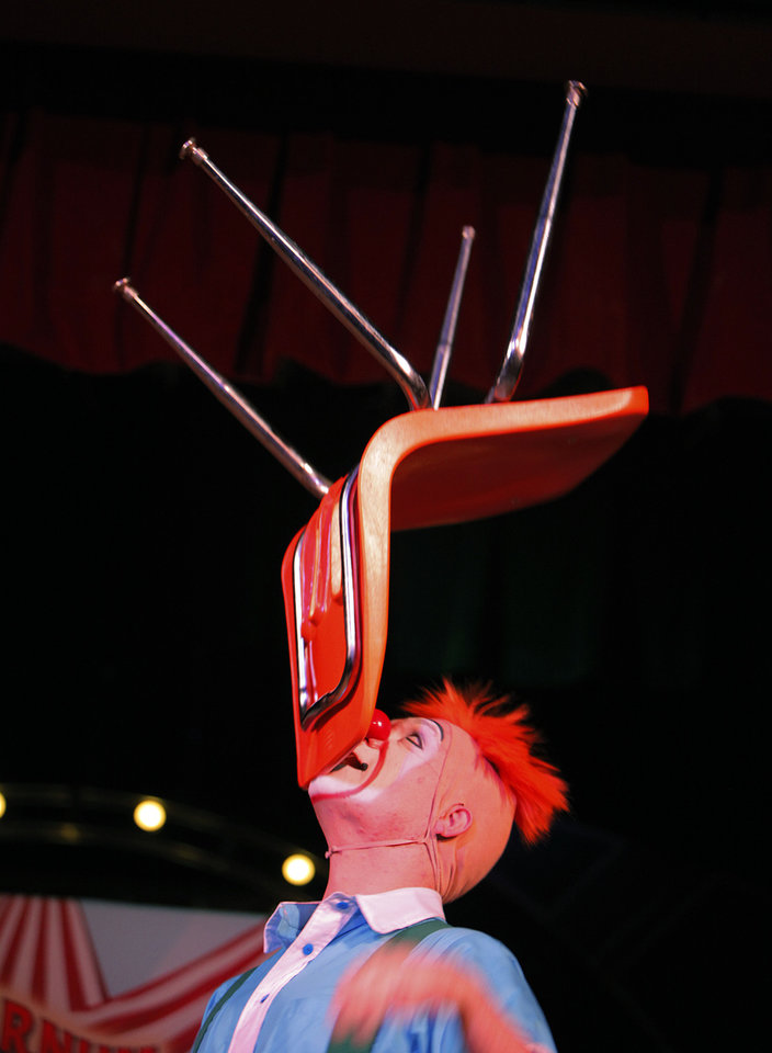 Photo - Jordan Bunce balances a chair on his chin during a Science Live show at Science Museum Oklahoma, featuring Ringling Bros. and Barnum &  Bailey clowns. Photos by Garett Fisbeck, The Oklahoman
