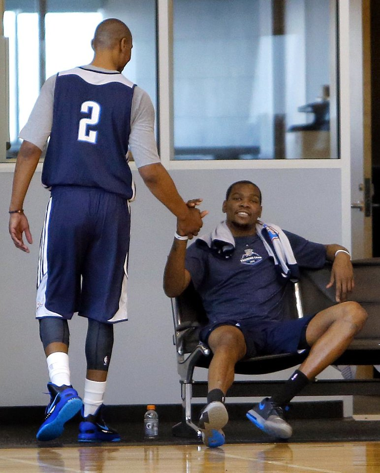 Photo - Caron Butler shakes hands with Kevin Durant after Bulter made his first practice appearance with the Oklahoma City Thunder at the Oklahoma City Thunder practice facility in Oklahoma City, Okla. on Monday, March 3, 2014.  PHOTO BY CHRIS LANDSBERGER, The Oklahoman