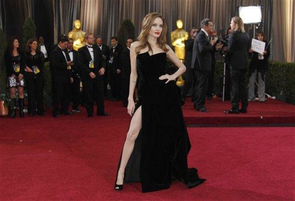 Photo - FILE - This Feb. 26, 2012 file photo shows Angelina Jolie posing before the 84th Academy Awards in the Hollywood section of Los Angeles. Every year fashion offers up the good, the bad and the ugly. But what the industry is really built on _ and consumers respond to _ is buzz. Jolie's leg, that peeked out of the high thigh-high slit of her Versace gown, was the most exciting appearance on the red carpet. (AP Photo/Amy Sancetta, file)