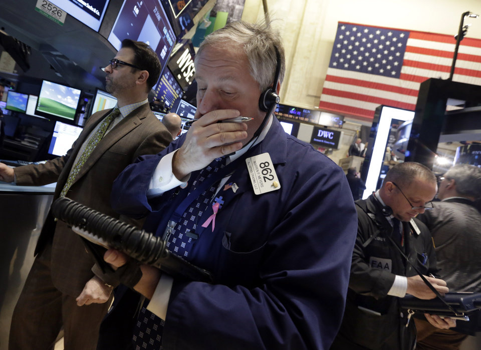 Photo - Trader Warren Meyers, center, works on the floor of the New York Stock Exchange Tuesday, Jan. 28, 2014. Stocks are higher in early trading on Wall Street as the stock market turns positive after three days of losses. (AP Photo/Richard Drew)