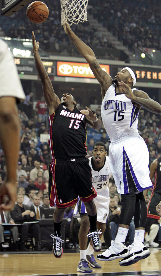 Miami Heat guard Mario Chalmers, left, drives to the basket against Sacramento Kings center DeMarcus Cousins, right,  during the first quarter of an NBA basketball game in Sacramento, Calif., Saturday, Jan. 12, 2013. (AP Photo/Rich Pedroncelli)