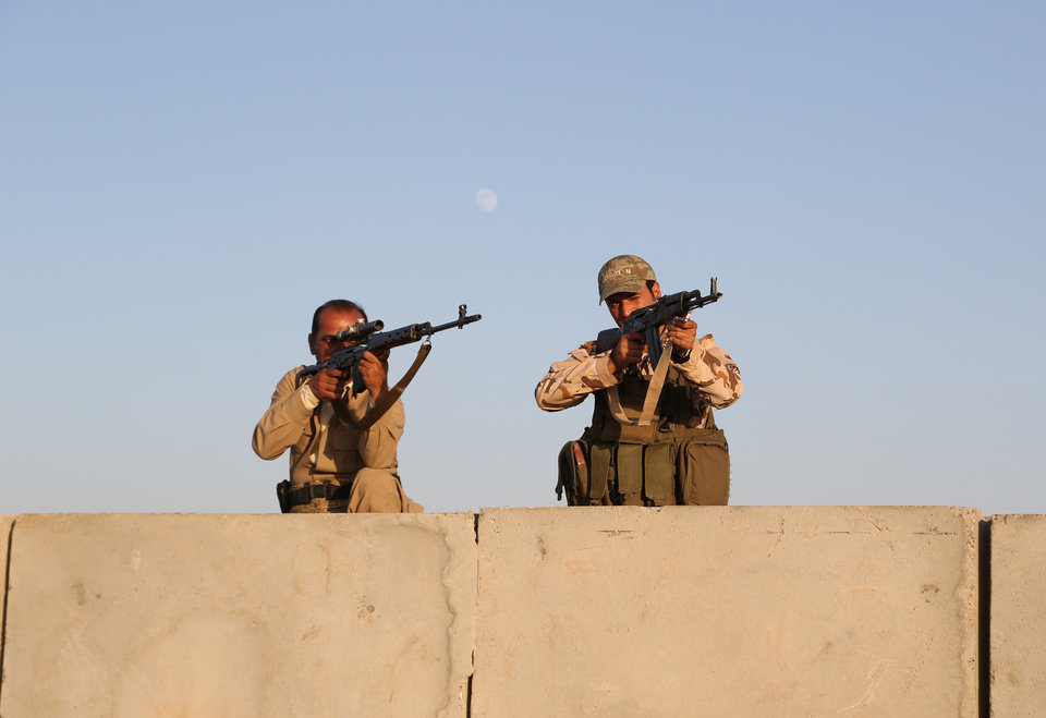 Photo - Kurdish Peshmerga fighters stand guard during airstrikes targeting Islamic State militants at the Khazer checkpoint outside of the city of Irbil in northern Iraq, Friday, Aug. 8, 2014. Iraqi Air Force has been carrying out strikes against the militants, and for the first time on Friday, U.S. war planes have directly targeted the extremist Islamic State group, which controls large areas of Syria and Iraq. (AP Photo/ Khalid Mohammed)