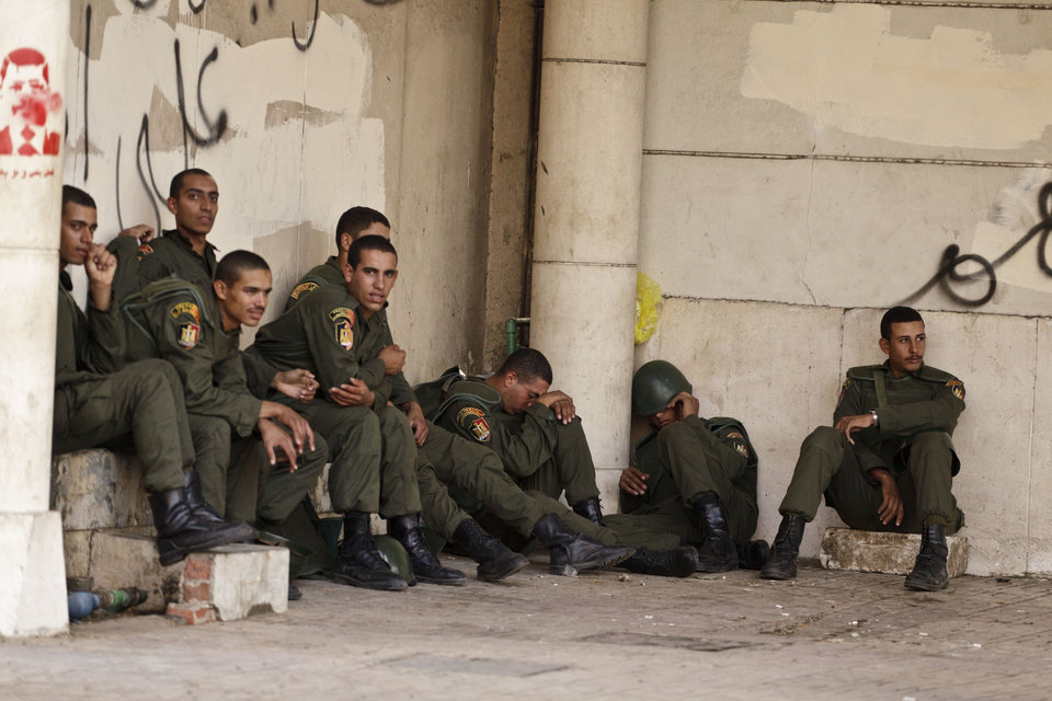 Photo - Egyptian presidential guards rest as protesters opposed to Egyptian President Mohammed Morsi gather outside the palace in Cairo, Egypt, Saturday, Dec. 8, 2012. Egypt's military said Saturday that serious dialogue is the
