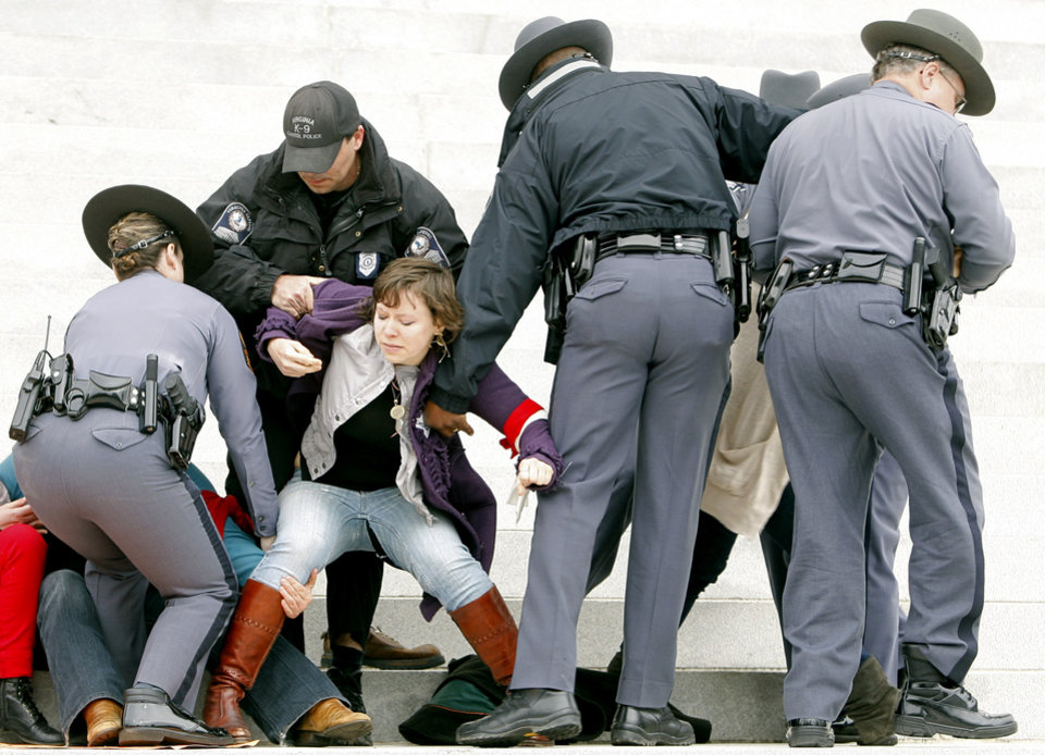 Protesters are removed from the front steps of the State Capitol in Richmond, Va., Saturday, March 3, 2012. Virginia Capitol Police arrested more than 30 women's rights activists Saturday when they refused to leave the Capitol steps during a protest of anti-abortion legislation. The protesters were some of an estimated 500 who had marched down a downtown street before gathering on the Capitol grounds to protest legislation like a bill that passed the General Assembly earlier in the week that requires an ultrasound before an abortion.  (AP Photo/Richmond Times-Dispatch, Eva Russo)
