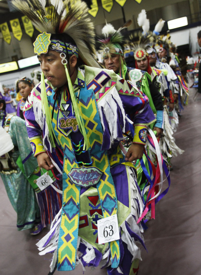 Photo -  Wolf Leitka, of Norman, leads a group into the arena during the grand entrance at the University of Central Oklahoma's annual Spring Powwow. PHOTO BY K.T. KING, THE OKLAHOMAN   KT King -