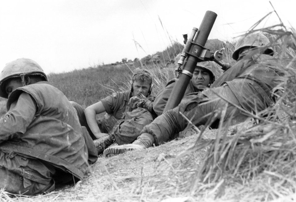 """Photo - FILE -in this March 3, 1967 file photo, two U.S. Marines hug the ground in high grass on hill 162, position of the 1st Batt./9th marines next to a 81 mm Mortar while North Vietnamese Mortar crews bombard the marines' positions, in Vietnam. The Marine Corps is holding a deactivation ceremony on Friday, Aug. 29, 2014, for the 1st Battalion, 9th Marine Regiment, 2nd Marine Division, a battalion nicknamed the """"Walking Dead."""" (AP Photo/Kim Ki Sam)"""