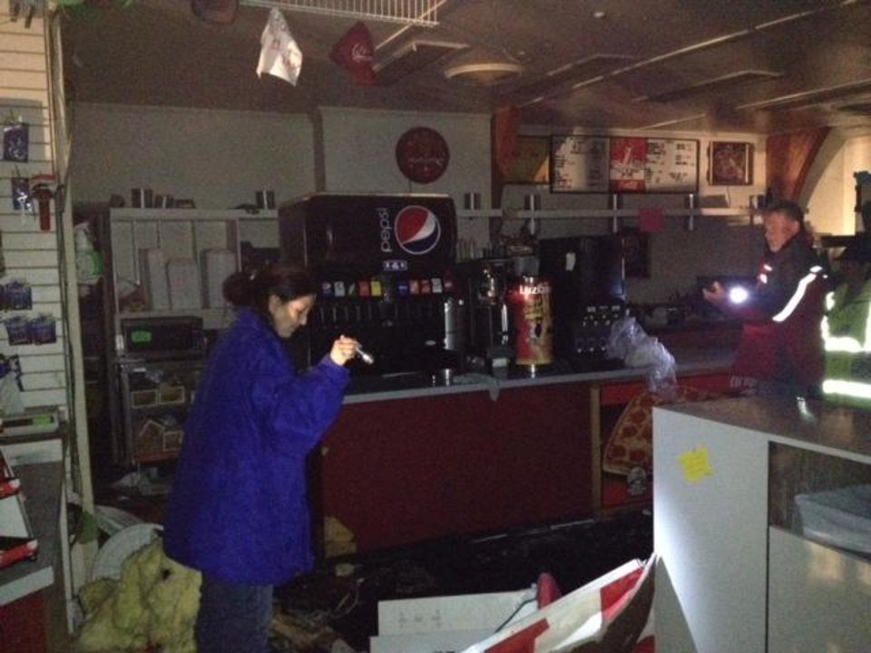 Photo - Debbie Ulloa looks at damage done to her business by tornado. Shell Food Plaza at I-40 & Banner Rd. There was extensive roof and window damage to the building. Photo by Jim Beckel, The Oklahoman.