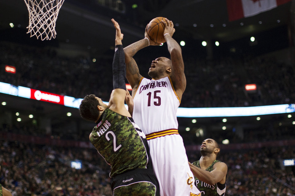 Cleveland Cavaliers' Marreese Speights (15) drives to the basket between Toronto Raptors' Landry Fields (2) and Alan Anderson during the first half of an NBA basketball game, Saturday, Jan. 26, 2013, in Toronto. (AP Photo/The Canadian Press, Chris Young)