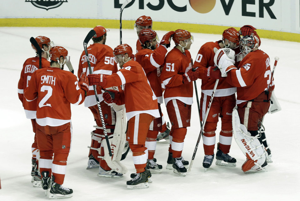 Photo - Detroit Red Wings players celebrate their 2-0 win over the Chicago Blackhawks after Game 4 of the Western Conference semifinals in the NHL hockey Stanley Cup playoffs in Detroit, Thursday, May 23, 2013. (AP Photo/Paul Sancya)
