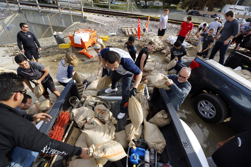 Photo - Volunteers fill sandbags in the City of Glendora, Calif., Thursday, Feb. 27, 2014. Residents with the help of their city, prepare for possible flooding. In advance of a powerful Pacific storm, mandatory evacuation orders have been issued for 1,000 homes in Glendora and Azusa, two of Los Angeles' eastern foothill suburbs, which are located beneath nearly 2,000 acres of steep mountain slopes left bare by a January fire. (AP Photo/Damian Dovarganes)