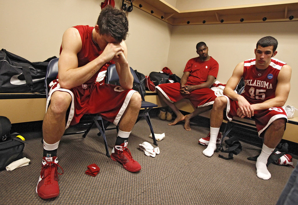 Photo - Oklahoma's Cade Davis, left, reacts in the locker room after the Sooners 72-60 loss to North Carolina in the Elite Eight game of NCAA Men's Basketball Regional between the University of North Carolina and the University of Oklahoma at the FedEx Forum on Sunday, March 29, 2009, in Memphis, Tenn.