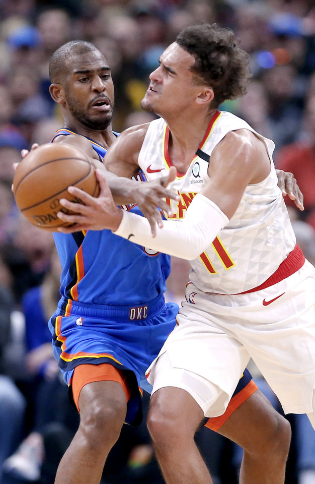 Photo - Oklahoma City's Chris Paul (3) fouls Atlanta's Trae Young (11) after a rip move