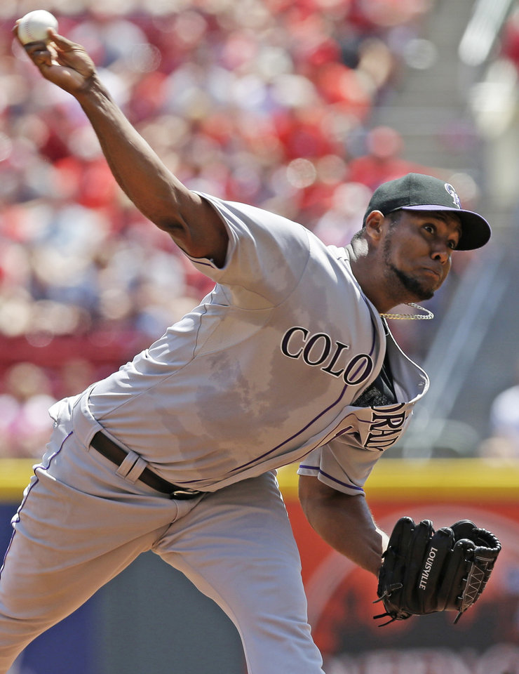 Photo - Colorado Rockies starting pitcher Juan Nicasio throws against the Cincinnati Reds in the first inning of a baseball game, Sunday, May 11, 2014, in Cincinnati. (AP Photo/Al Behrman)