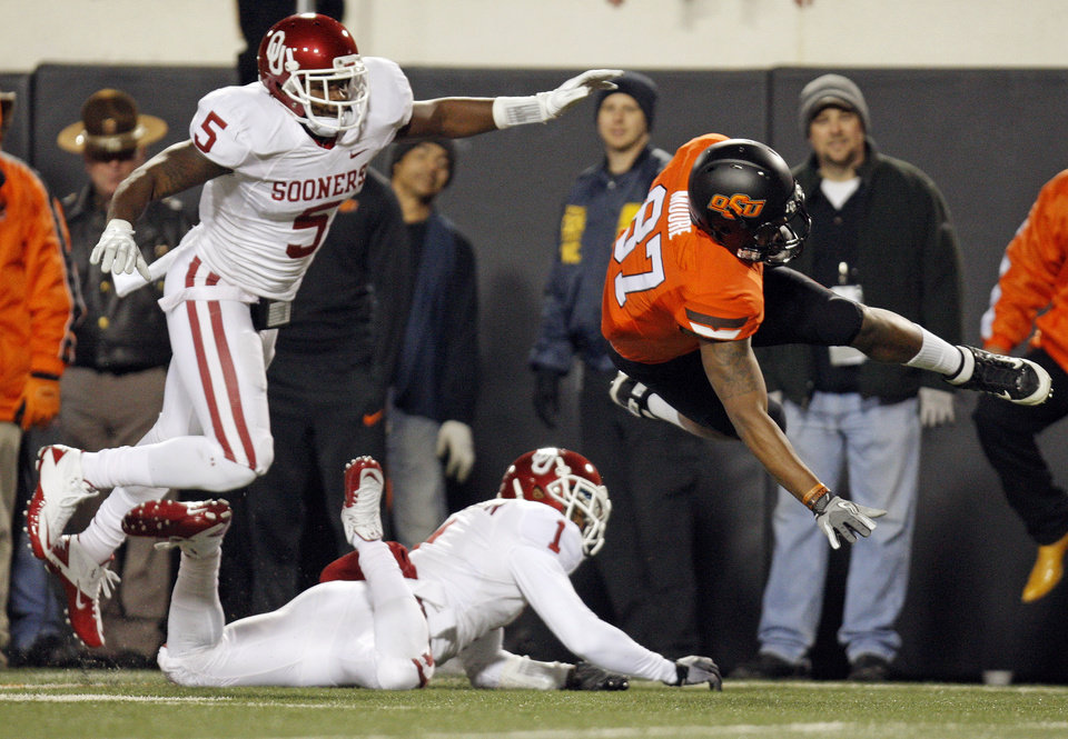 Photo - OSU's Tracy Moore (87) is tripped up by OU's Tony Jefferson (1) in front of Joseph Ibiloye (5) in the first quarter during the Bedlam college football game between the Oklahoma State University Cowboys (OSU) and the University of Oklahoma Sooners (OU) at Boone Pickens Stadium in Stillwater, Okla., Saturday, Dec. 3, 2011. Photo by Nate Billings, The Oklahoman