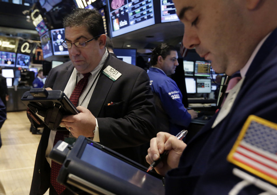 Photo - Traders Robert Oswald, left, and Fred DeMarco work on the floor of the New York Stock Exchange, Thursday, Dec. 19, 2013. Stocks edged lower in early trading Thursday, pulling back from record levels. (AP Photo/Richard Drew)