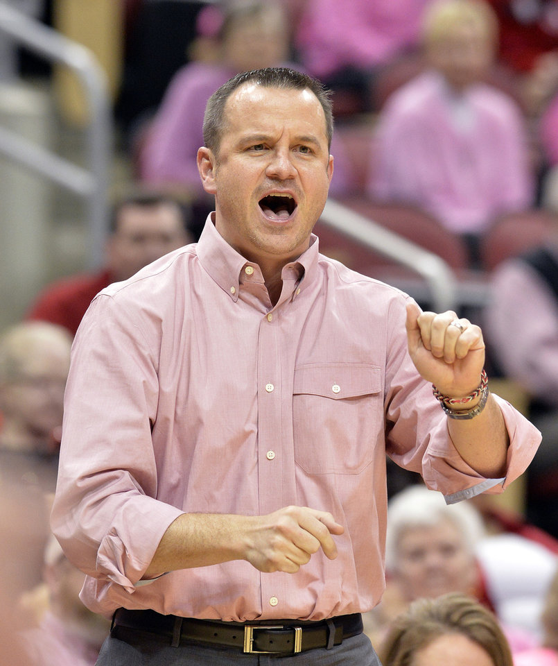 Photo - Louisville head coach Jeff Walz shouts instructions to his team during the first half of an NCAA college basketball game against Rutgers, Sunday, Feb. 23, 2014, in Louisville, Ky. (AP Photo/Timothy D. Easley)