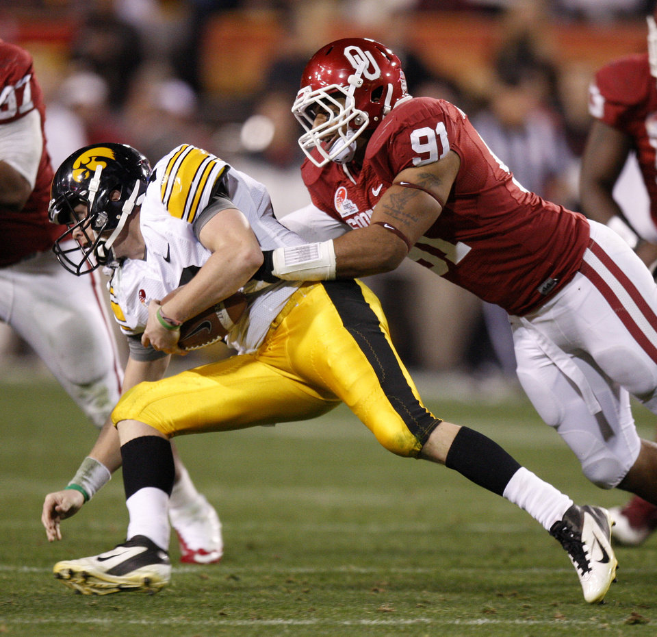 Photo - Oklahoma's R.J. Washington (91) brings down Iowa's James Vandenberg (16) during the Insight Bowl college football game between the University of Oklahoma (OU) Sooners and the Iowa Hawkeyes at Sun Devil Stadium in Tempe, Ariz., Friday, Dec. 30, 2011. Photo by Bryan Terry, The Oklahoman