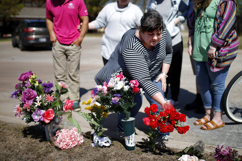Photo -  Neighbor Sandy McLerran places flower near the home of Cecille Short, who was mauled to death by two large dogs. [Photo by Bryan Terry, The Oklahoman]