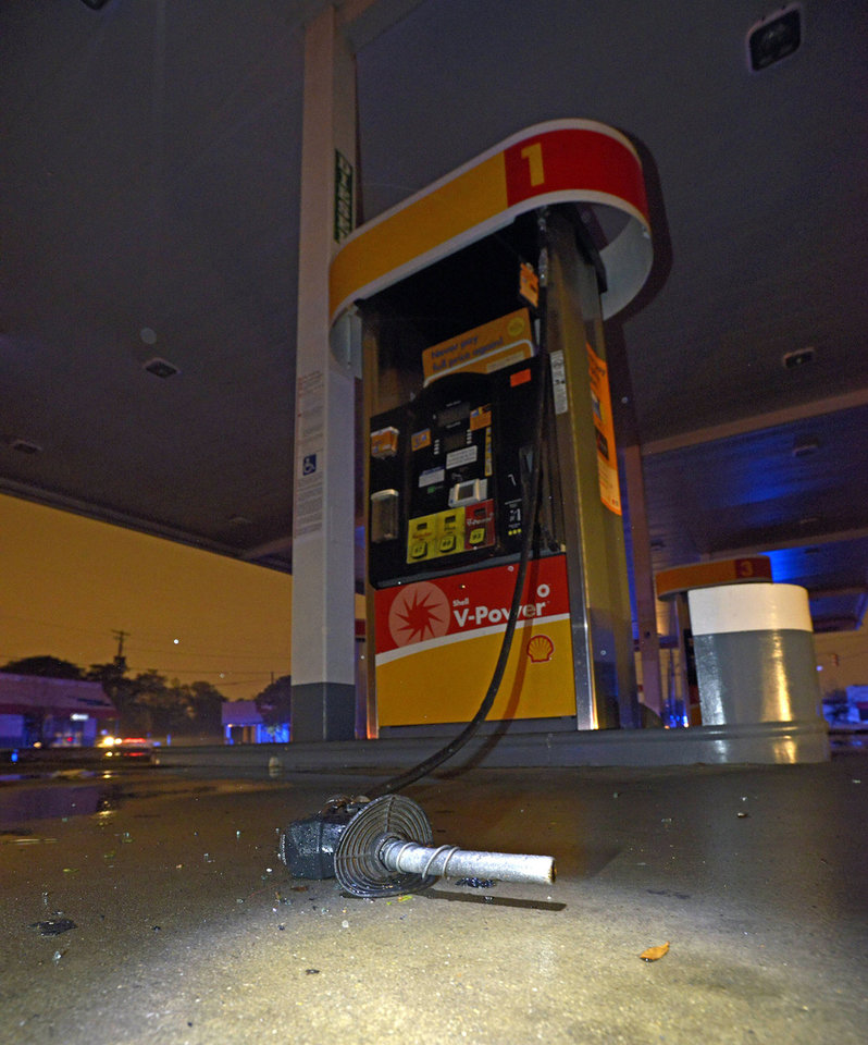 Photo - The nozzle of a gasoline pump sits on the ground after being blown from its pump after a tornado touched down Tuesday, Dec. 25, 2012 in Mobile, Ala. A Christmas Day twister outbreak left damage across the Deep South while holiday travelers in the nation's much colder midsection battled sometimes treacherous driving conditions from freezing rain and blizzard conditions. (AP Photo/G.M. Andrews)