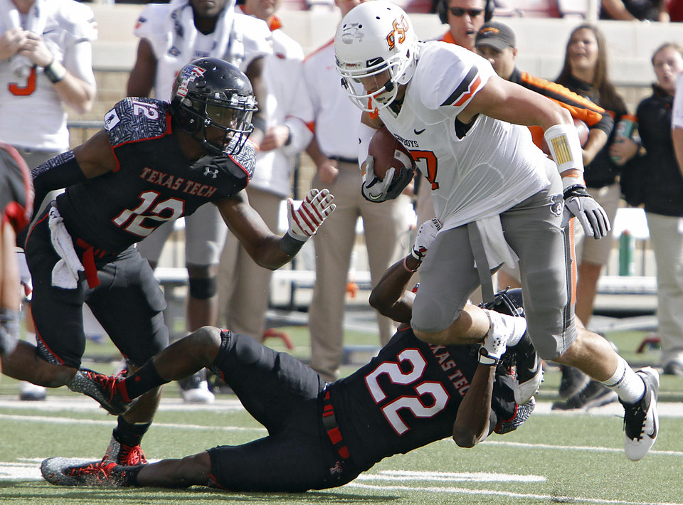 Texas Tech Red Raiders safety D.J. Johnson (12) and Jared Flannel (22) try to bring down Oklahoma State Cowboys wide receiver Charlie Moore (17) during the college football game between the Oklahoma State University Cowboys (OSU) and Texas Tech University Red Raiders (TTU) at Jones AT&T Stadium on Saturday, Nov. 12, 2011. in Lubbock, Texas. Photo by Chris Landsberger, The Oklahoman ORG XMIT: KOD