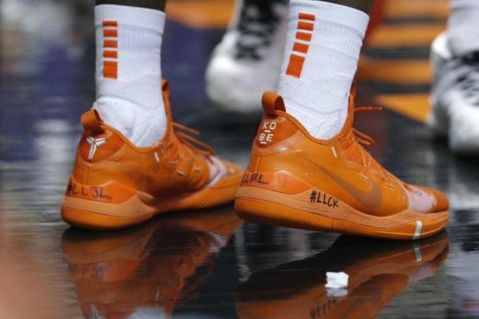 Photo -  Oklahoma State's Isaac Likekele shoes feature three tributes to his grandfather Rafael, friend John Lee and friend Criston King. [Bryan Terry/The Oklahoman]