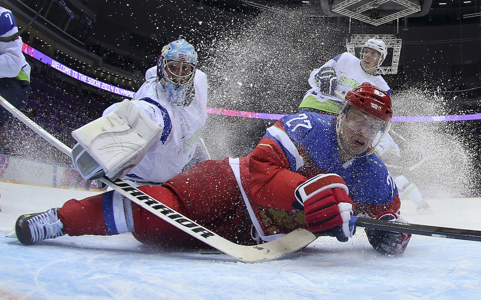 Photo - Slovenia goaltender Robert Kristan reaches over Russia forward Alexei Tereshenko as they fall to the ice at the goal in the first period of a men's ice hockey game at the 2014 Winter Olympics, Thursday, Feb. 13, 2014, in Sochi, Russia. Russia won 5-2. (AP Photo/Bruce Bennett, Pool)