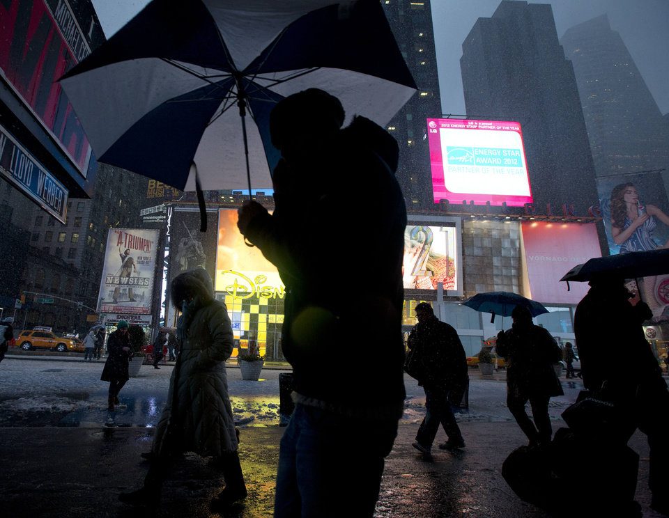 Photo - Pedestrians use umbrellas to shield themselves from the snow as they walk through Times Square Friday, Feb. 8, 2013, in New York. Snow began falling across the Northeast on Friday, ushering in what was predicted to be a huge, possibly historic blizzard and sending residents scurrying to stock up on food and gas up their cars. The storm could dump 1 to 3 feet of snow from New York City to Boston and beyond. (AP Photo/Frank Franklin II)