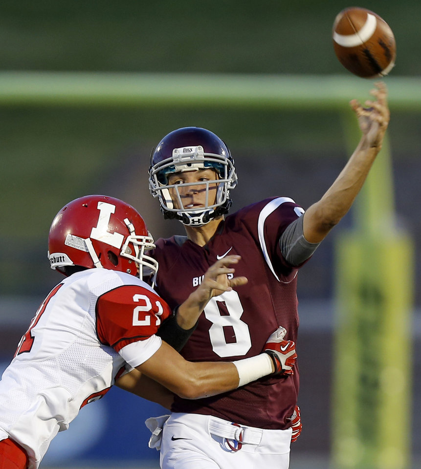 Edmond Memorial's Luke Booker is hit by Lawton's Matt Leon as he throws during their high school football game at Wantland Stadium in Edmond, Okla., Friday, Sept. 27, 2013. Photo by Bryan Terry, The Oklahoman
