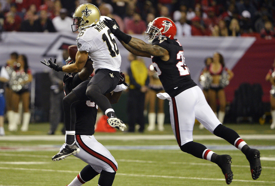 Photo - New Orleans Saints wide receiver Lance Moore (16) makes a catch between Atlanta Falcons' Sean Weatherspoon, obscured, and Charles Mitchell (26) during the first half of an NFL football game, Thursday, Nov. 29, 2012, in Atlanta. (AP Photo/Rich Addicks)