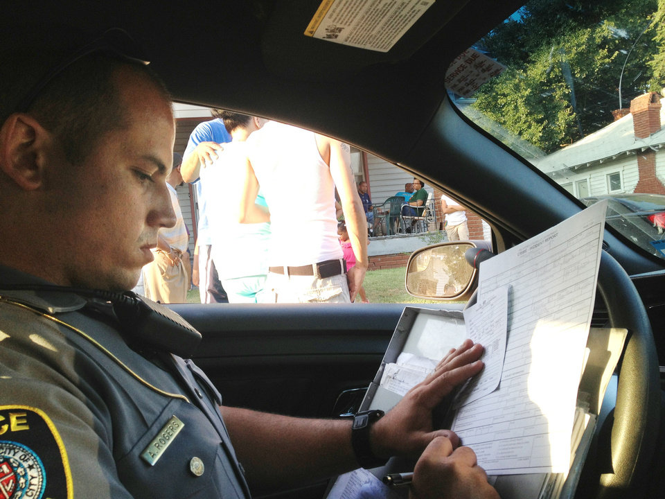 Photo - Oklahoma City police officer Adam Rogers fills out a police incident report during a Sept. 11 call in northeast Oklahoma City. During a patrol for about three hours the evening of Wed., Sept. 11, Rogers responded to a number of calls. Among the incidents that required police response were a call regarding an elderly man who had died, a 911 call regarding an assault with a deadly weapon, a report of men harassing women from a parking lot and a report of juveniles fighting in an apartment complex. Photo by Juliana Keeping, The Oklahoman  Julianna Keeping