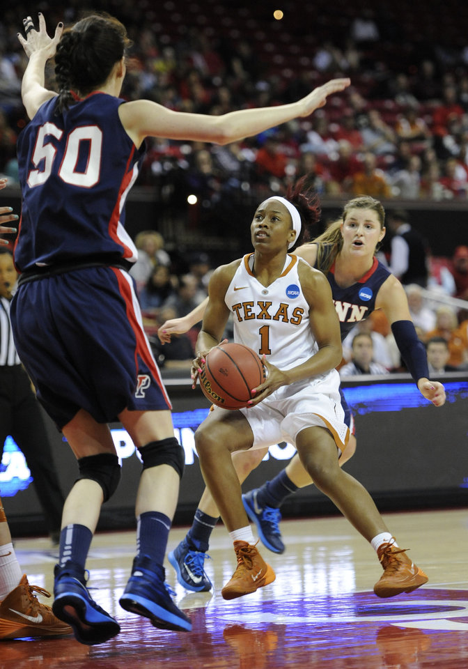 Photo - Texas' Empress Davenport (1) drives to the basket as Penn's Courtney Wilson, left, and Alyssa Baron defend during the first half of the first round of the NCAA women's college basketball tournament on Sunday, March 23, 2014, in College Park, Md. (AP Photo/Gail Burton)
