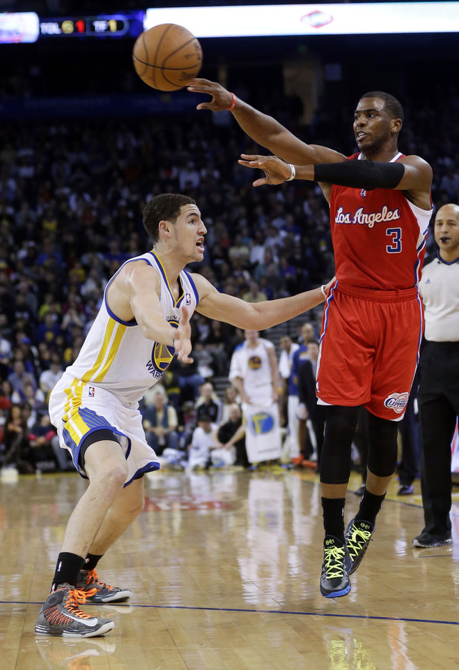 Los Angeles Clippers' Chris Paul (3) passes over Golden State Warriors' Klay Thompson during the first half of an NBA basketball game in Oakland, Calif., Monday, Jan. 21, 2013. (AP Photo/Marcio Jose Sanchez)