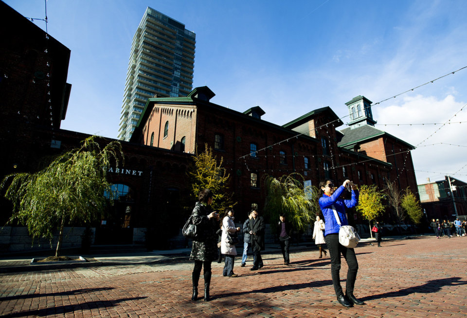 Photo -   This Nov. 14, 2012 photo shows people taking photographs as they walk around at the historical Distillery District in Toronto. This quaint East End area has been turned into an enclave of art galleries, restaurants and boutiques offering one-of-a-kind fare such as hand-crafted jewelry housed in restored heritage Victorian buildings. (AP Photo/The Canadian Press, Nathan Denette)
