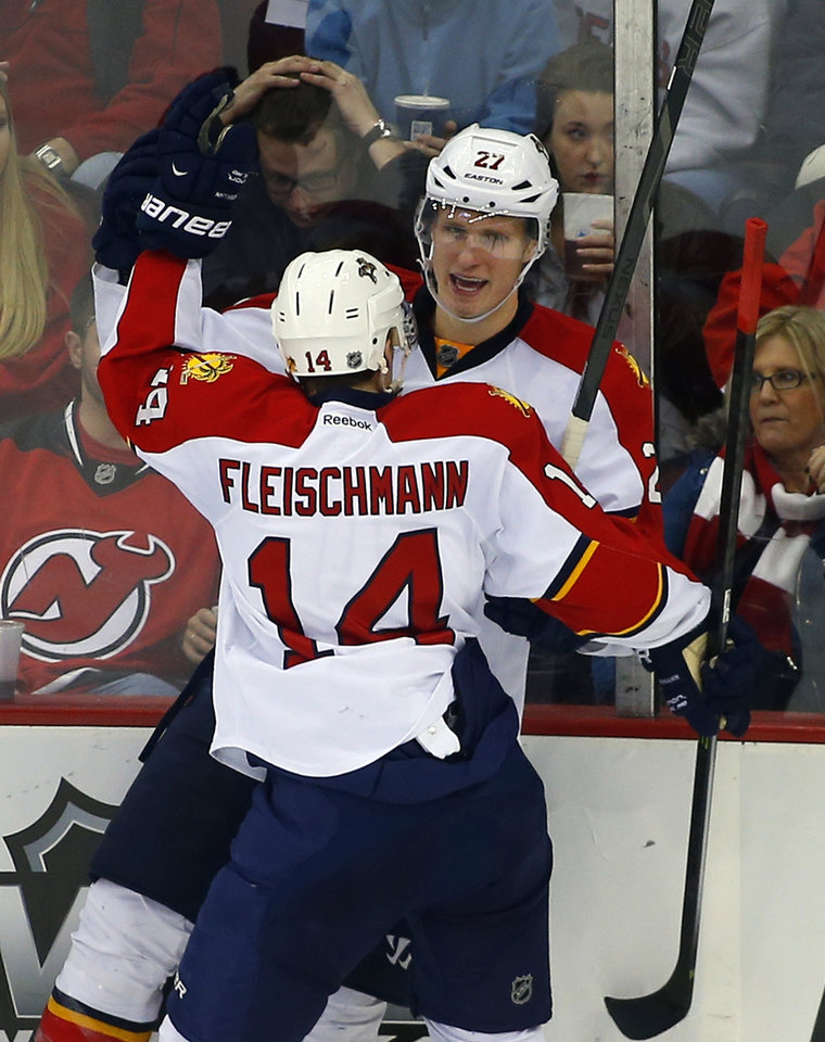 Photo - Florida Panthers' Nick Bjugstad (27) celebrates his goal with teammate Tomas Fleischmann (14), of the Czech Republic, against the New Jersey Devils during the second period of an NHL hockey game in Newark, N.J., Saturday, Jan. 11, 2014. (AP Photo/Rich Schultz)