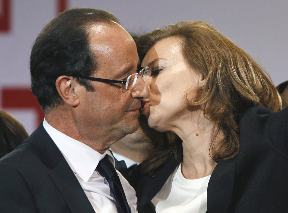 Photo - FILE - This Sunday, May 6, 2012, file photo shows French president-elect Francois Hollande kissing his companion, Valerie Trierweiler, after greeting crowds gathered to celebrate his election victory in Bastille Square in Paris. Hollande is threatening legal action over magazine report saying he is having a secret affair with a French actress. The magazine Closer published images Friday Jan.10, 2014 showing his bodyguard and a helmeted man it says is Hollande visiting what it says is the apartment of the actress. (AP Photo/Francois Mori, File)