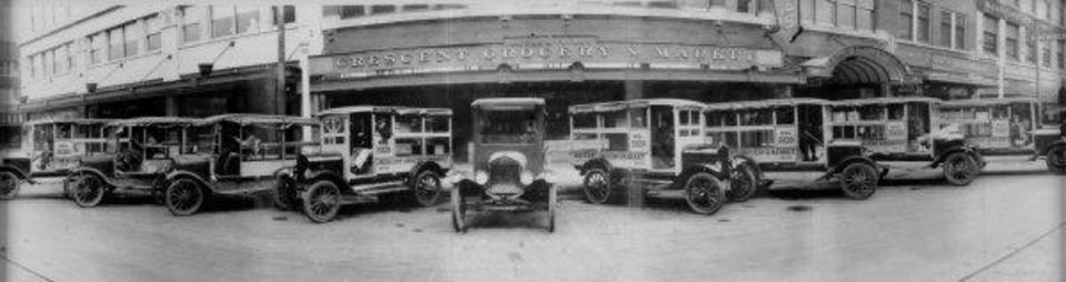 Model T delivery trucks line Main Street in front of Crescent Market during the 1920s. At one point the grocery store operated 11 delivery trucks. <strong>COPY</strong>