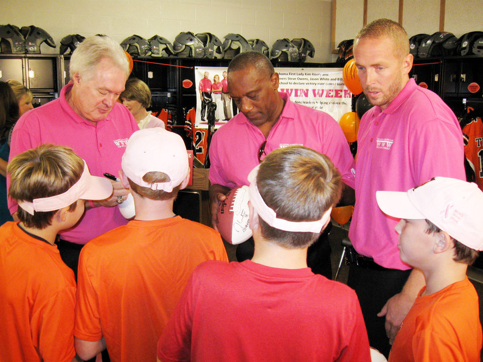 Photo - From left, Former University of Oklahoma players and Heisman Trophy winners Steve Owens, Billy Sims and Jason White sign autographs and meet a few young fans Monday at the Norman High School fieldhouse after an announcement for the Oklahoma Students Care