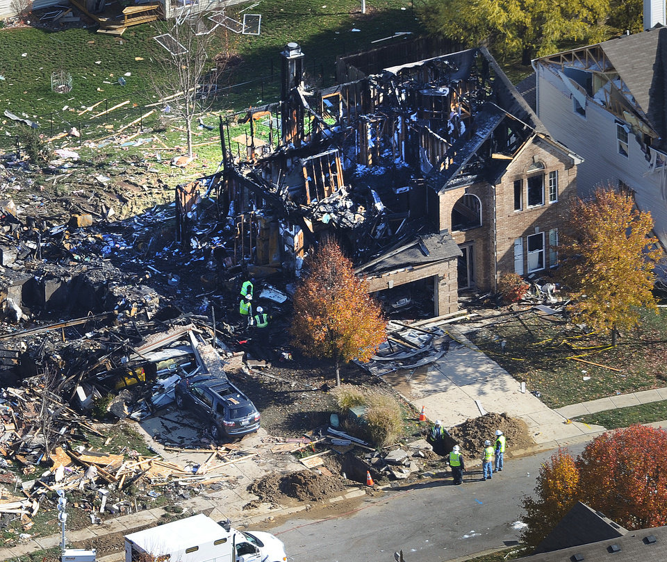Citizens Energy workers continue their investigation Monday afternoon Nov. 12, 2012 by digging into the front sidewalk looking for possible explanation into the explosion of a house in Indianapolis. The search for what caused a massive, deadly explosion that rocked an Indianapolis neighborhood turned to natural gas Monday, with officials checking gas lines and a homeowner saying a problem furnace could be to blame. (AP Photo/WTHR Chopper 13/The Indianapolis Star, Matt Kryger) NO SALES