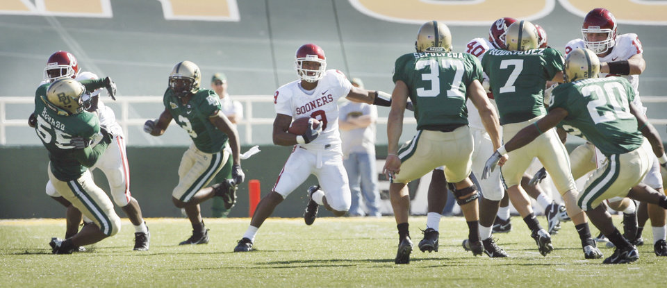 Photo - Juaquin Iglesias takes a free kick after the safety for a score in the second half during the University of Oklahoma Sooners (OU) college football game against Baylor University Bears (BU) at Floyd Casey Stadium, on Saturday, Nov. 18, 2006, in Waco, Texas.  The kicker Daniel Sepulveda (37) is one of the would-be tacklers.     by Steve Sisney, The Oklahoman
