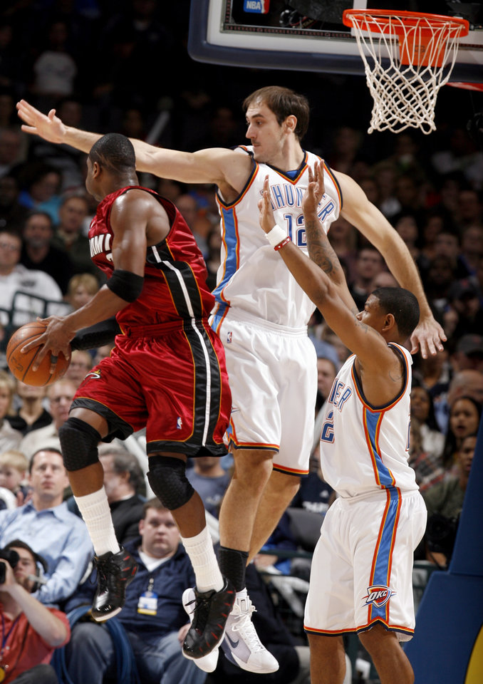 Oklahoma City\'s Nenad Krstic (12) and Earl Watson (25) defend Miami\'s Dwyane Wade (3) as he passes the ball during the NBA game between the Oklahoma City Thunder and the Miami Heat Sunday Jan. 18, 2009, at the Ford Center in Oklahoma City. PHOTO BY SARAH PHIPPS, THE OKLAHOMAN