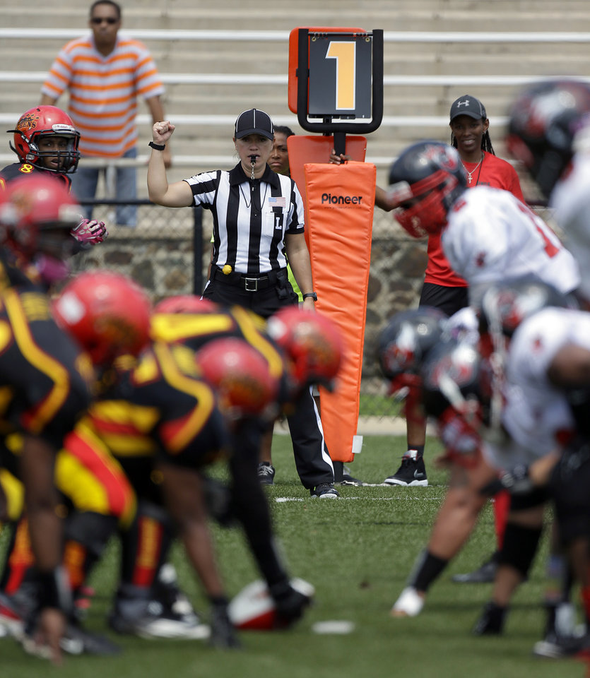 Photo - In a photo provided by the NFL, line judge Catherine Conti signals from the sideline at the Legacy Bowl Women's Football Championship, on Friday July 25, 2014, in Rock Hill, S.C. The 38-year-old Conti had been assigned to the Southeast Missouri State-Kansas game on Sept. 6, making her the first woman to work a football game in the Big 12 Conference. Conti will work mostly as a line judge in the Mountain West for the second straight year. She landed the Big 12 gig through the league's officiating partnership with the Mountain West and FCS-level Southland Conference. (AP Photo/NFL, Bob Leverone)