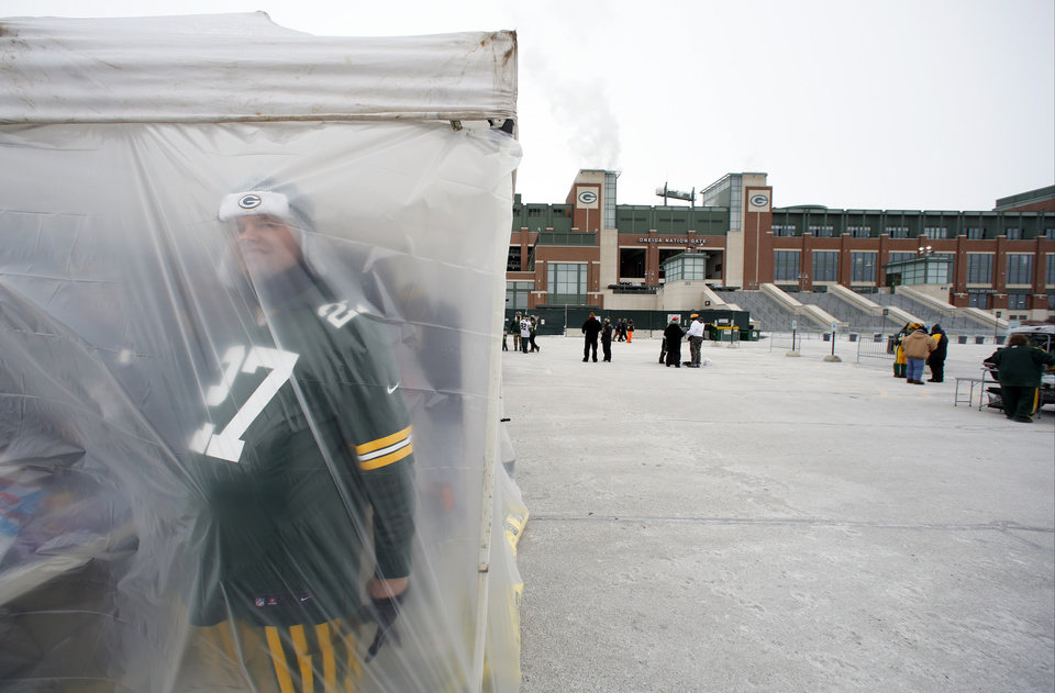 Photo - A Green Bay Packers fan looks through a tent as fans tailgate before an NFL wild-card playoff football game between the Green Bay Packers and the San Francisco 49ers, Sunday, Jan. 5, 2014, in Green Bay, Wis. (AP Photo/Jeffrey Phelps)