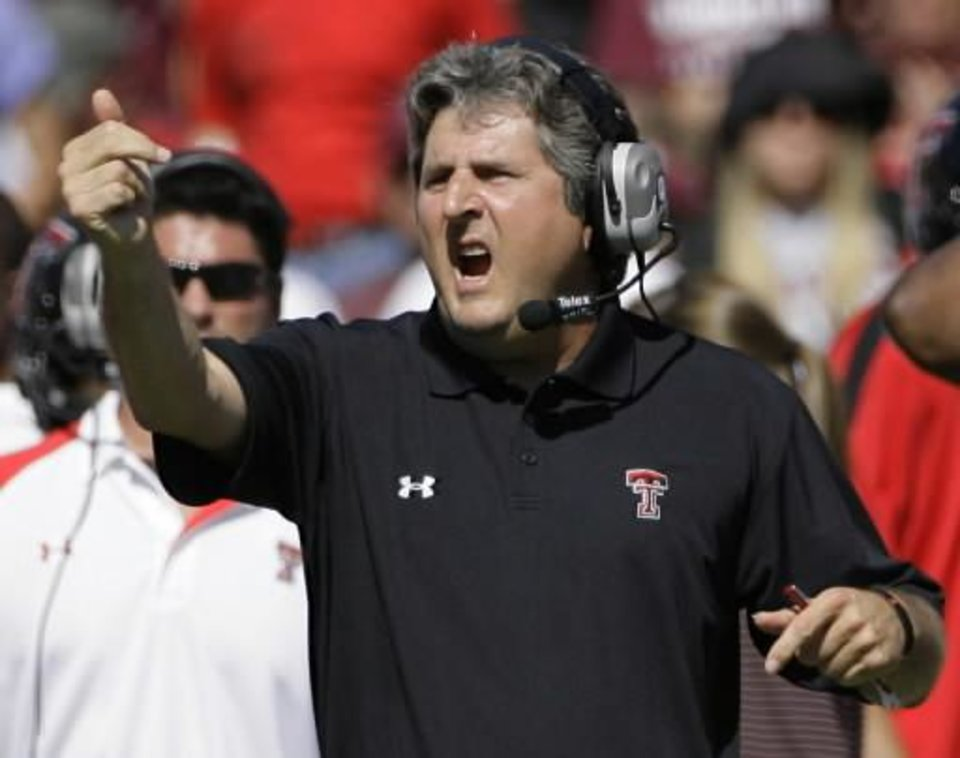 Photo - Texas Tech head coach  Mike  Leach calls to his team during a time-out in the second half of an NCAA college football game against Texas A&M, Saturday, Oct. 18, 2008, in College Station, Texas. Texas Tech won 43-25. (AP Photo/Matt Slocum)