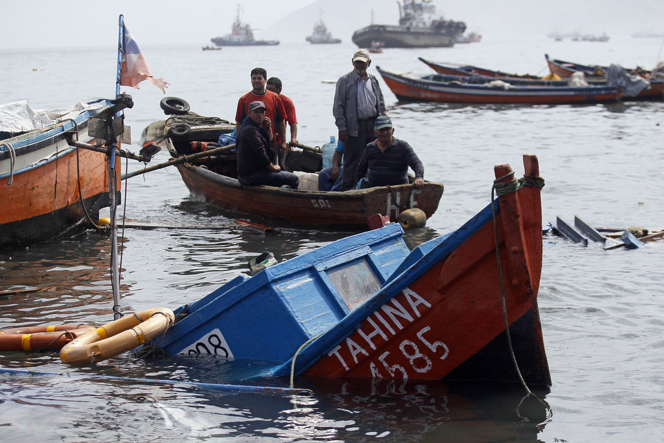 Photo - Fishermen look for boats to salvage damaged overnight in the port of Iquique, Chile, Wednesday, April 2, 2014. Chilean authorities discovered surprisingly light damage Wednesday from a magnitude-8.2 quake that struck in the Pacific Ocean, Tuesday evening, near the mining port of Iquique, a northern coastal city of nearly 200,000 people. Fishing boats were lifted onto city streets and others were sunk in the port. Six deaths have been reported. ( AP Photo/ Luis Hidalgo, Pool)